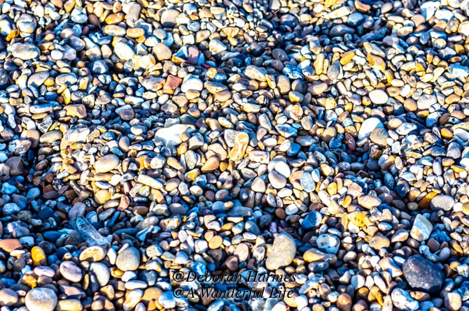 Close-up of a the beautifully coloured pieces of stone comprising a gravel beach, sometimes called a shingle beach, in the UK.