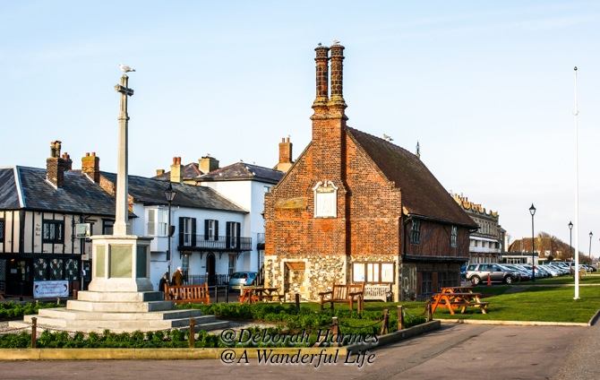 Medieval Moot Hall in Aldeburgh, Suffolk, UK, built in 1520, with the village memorial cross to the left.