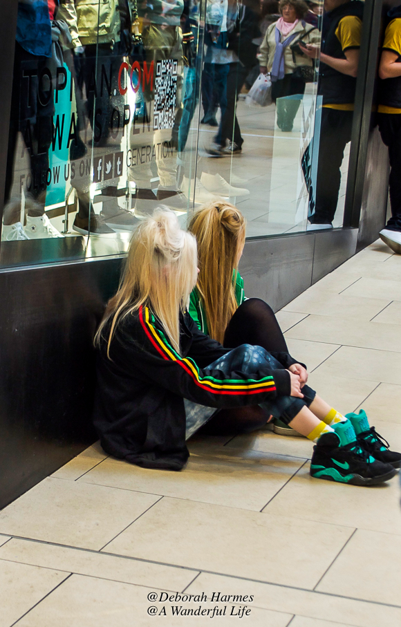 Two young girls with teased chunks of hair sitting on the floor in a shopping mall.