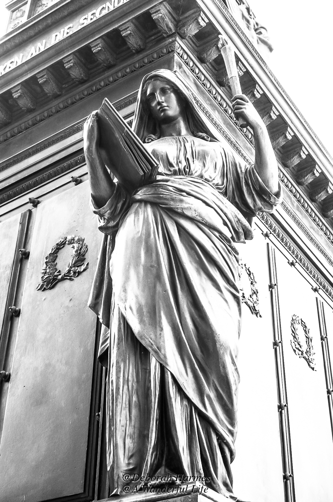 A sculpture of a serene woman at one of the 4 corners of the Friedrich August I monument in the Schlossplatz in Dresden, Germany.