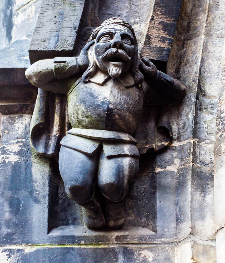 A detail of a startled man holding his head in his hands on one of the side arches of the medieval Marktkirche in Hannover, Germany.